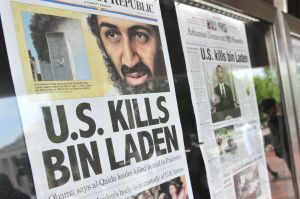 People look at newspaper headlines announcing the death of Osama Bin Laden in Washington